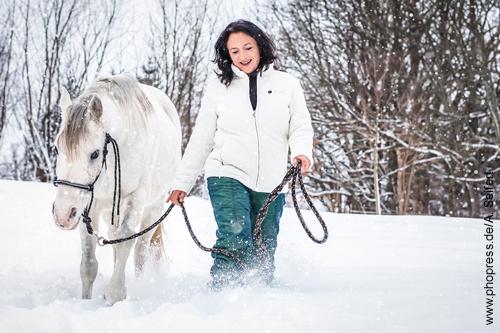 Antje Müller, Horse Assisted Coach, spaziert mit ihrer Stute durch den Tiefschnee.
