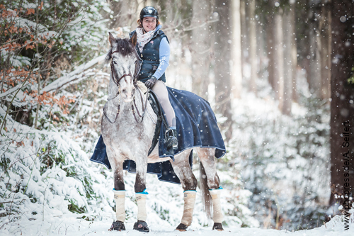 Junges Mädchen bei einem Ausritt in den Winterwald mit ihrem Wallach.